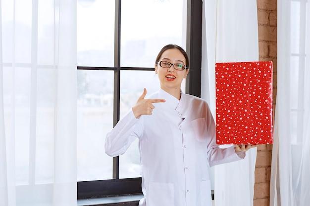 Mooie vrouw met bril in laboratoriumjas wijzend op grote huidige doos in de buurt van raam.