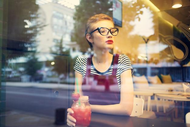 Mooie vrouw met bril ziet een eenzaam cocktaildrankje in een café