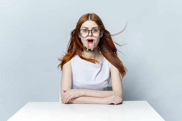 Mooie vrouw met bril zitten aan de tafel emoties capriolen