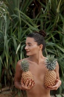 Mooie vrouw met bronzen kleur houdt ananas in handen