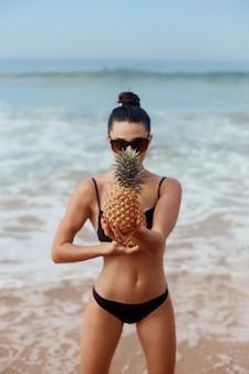 Mooie vrouw met bronzen kleurtje in bikini houdt ananas in handen