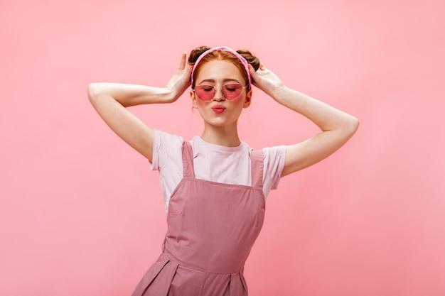 Mooie vrouw met broodjes gekleed in roze overall en wit t-shirt poseren met gesloten ogen op roze achtergrond.
