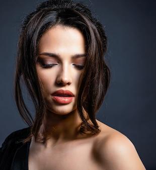 Mooie vrouw met bruin haar. aantrekkelijk model met bruine ogen. mannequin met een rokerige make-up. het close-upportret van een mooie vrouw bekijkt camera. creatief kapsel.