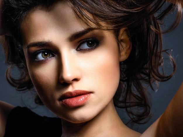 Mooie vrouw met bruin haar. aantrekkelijk model met bruine ogen. mannequin met een rokerige make-up. het close-upportret van een mooie vrouw bekijkt camera.