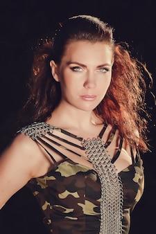 Mooie vrouw met bruin haar in militaire mode-kleding.