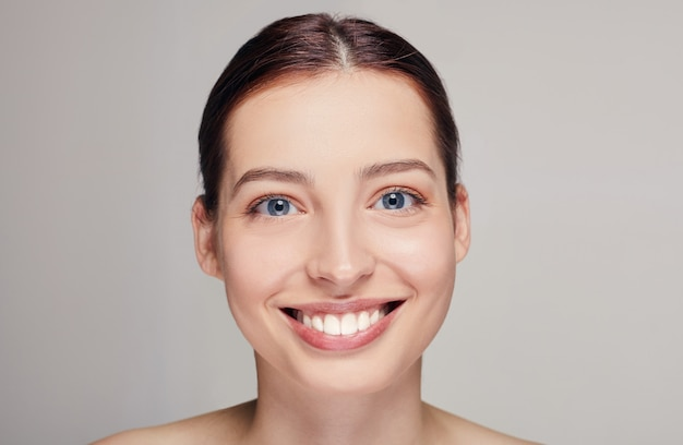Mooie vrouw met bruin haar, schone frisse huid die zich voordeed op een grijze studio, op zoek recht, breed glimlachend, model met lichte naakt make-up