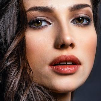 Mooie vrouw met bruine ogen. mannequin met een rokerige make-up. het close-upportret van een mooie vrouw bekijkt camera.