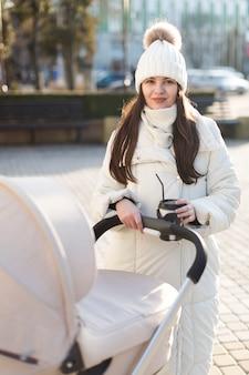 Mooie vrouw met buiten koffie en wandelwagen