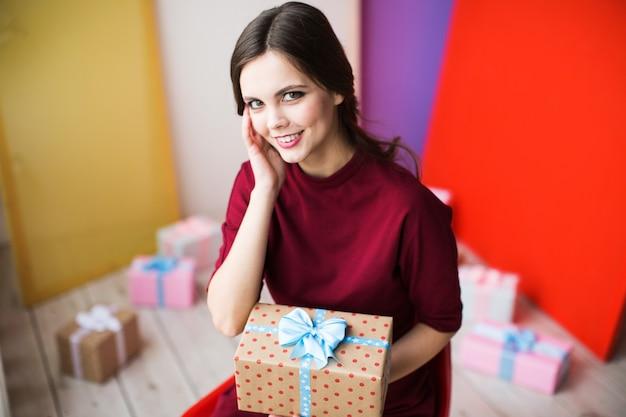 Mooie vrouw met cadeau op kleurrijke achtergrond.