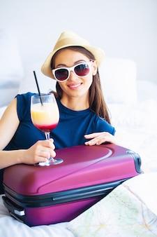 Mooie vrouw met cocktail en koffer op bed in hootelruimte
