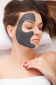 Mooie vrouw met cosmetische masker op gezicht. het meisje krijgt behandeling in kuuroordsalon tegen witte achtergrond