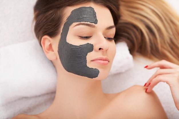 Mooie vrouw met cosmetische masker op gezicht.