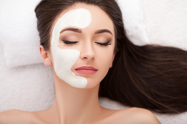 Mooie vrouw met cosmetische masker op gezicht