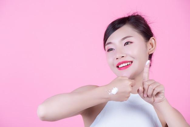 Mooie vrouw met crème op de huid op een roze achtergrond.