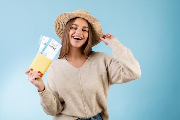 Mooie vrouw met de kaartjes van het instapkaartvliegtuig in paspoort en toeristenhoed die over blauw wordt geïsoleerd