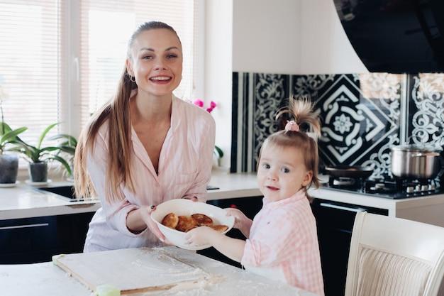Mooie vrouw met de mooie kom van de kindholding met koekjes