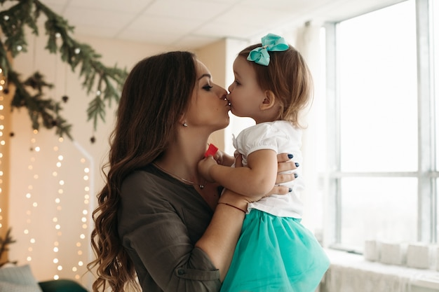 Mooie vrouw met dochter in handen, permanent in ingerichte studio met dennentakken en lichte garland