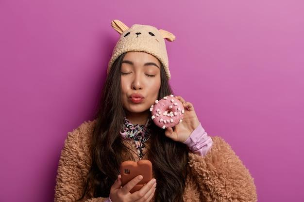 Mooie vrouw met donker lang haar, gebruikt mobiele telefoon, gebruikt moderne applicatie, houdt lippen gevouwen, houdt geglazuurde donut dichtbij gezicht