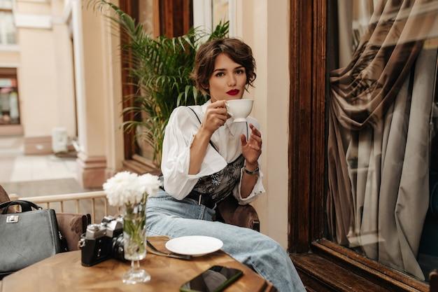 Mooie vrouw met donkerbruin haar in wit overhemd houdt kopje thee in café. stijlvolle vrouw met rode lippen en jeans met riem zit in restaurant.
