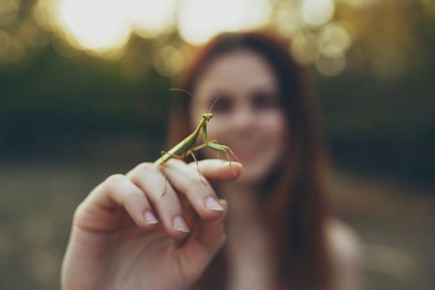 Mooie vrouw met een bidsprinkhaan in de hand wilde natuur