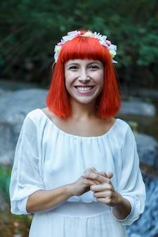 Mooie vrouw met een bloemkroonzitting dichtbij aan een waterval