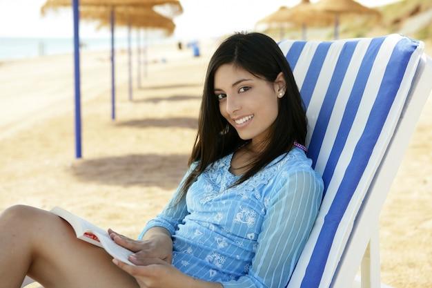 Mooie vrouw met een boek dat op het strand wordt ontspannen