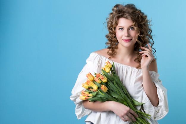 Mooie vrouw met een boeket van gele tulpen.