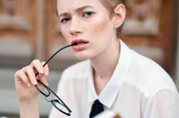Mooie vrouw met een bril die door de stad loopt met een boekcommunicatie