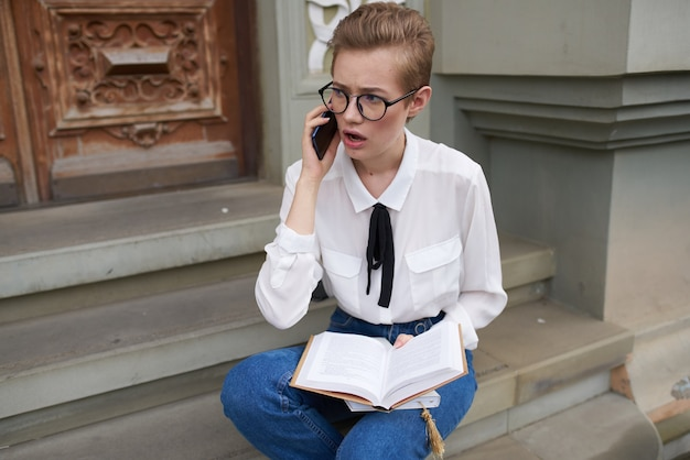 Mooie vrouw met een bril die door de stad loopt met een boekenlevensstijl