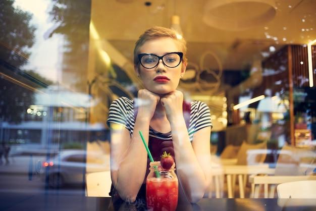 Mooie vrouw met een bril die in een restaurant zit van een levensstijl van cocktail-eenzaamheid