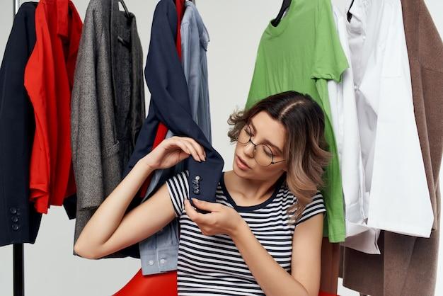 Mooie vrouw met een bril die kledingwinkel shopaholic lichte achtergrond probeert