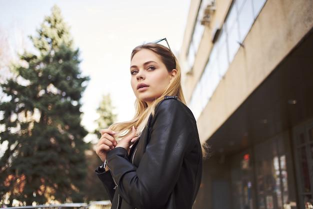Mooie vrouw met een bril in de buitenlucht, modewandeling in moderne stijl