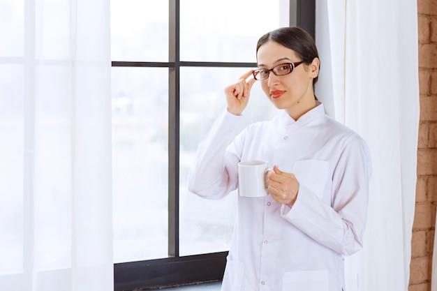 Mooie vrouw met een bril in laboratoriumjas staande terwijl ze een kopje koffie bij het raam houdt.