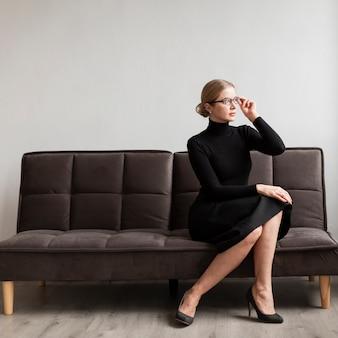 Mooie vrouw met een bril op de bank