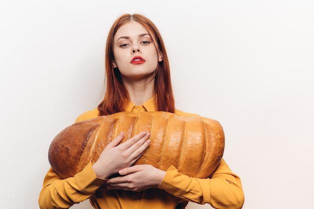 Mooie vrouw met een brood in haar handen en lichte make-up