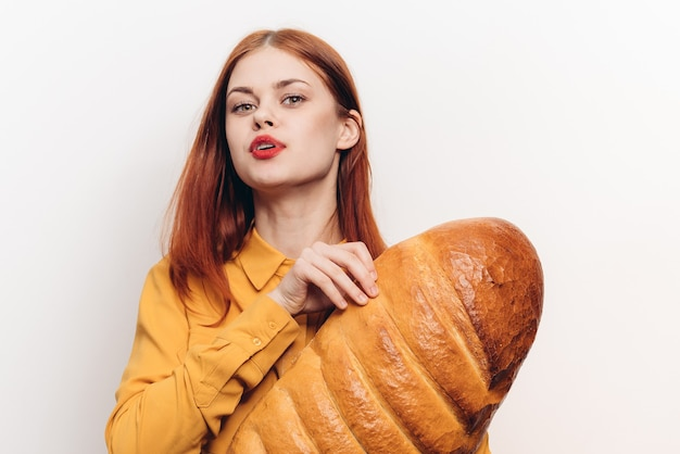 Mooie vrouw met een brood in haar handen op een licht de make-upmodel van muur rode lippen.
