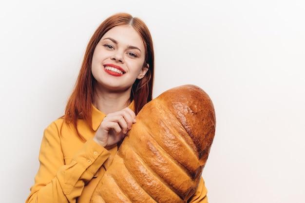 Mooie vrouw met een brood in haar handen op een lichtrood model van de lippenmake-up.
