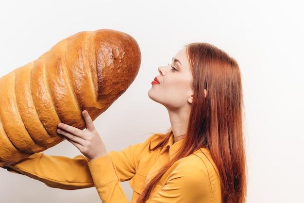 Mooie vrouw met een brood op een gekleurde achtergrond plezier emoties model