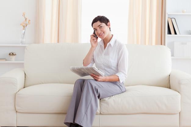 Mooie vrouw met een cellphone en een krant die bekijken