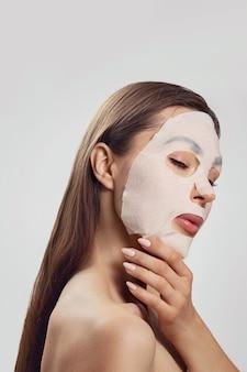 Mooie vrouw met een doek bevochtigend masker voor het gezicht. gezichts- en spabehandeling. cosmetisch masker.