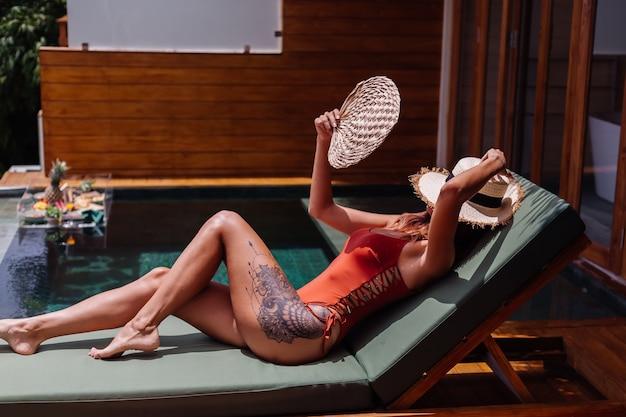 Mooie vrouw met een fit, perfect gebruind lichaam, bronzen huid, ligt op een groene zonnebank in een luxe tropische villa in een zwempak uit één stuk met een strohoedbedekking.
