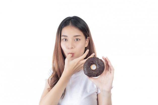 Mooie vrouw met een gelukkige glimlach die een handdoughnut houdt, die op witte achtergrond wordt geïsoleerd.