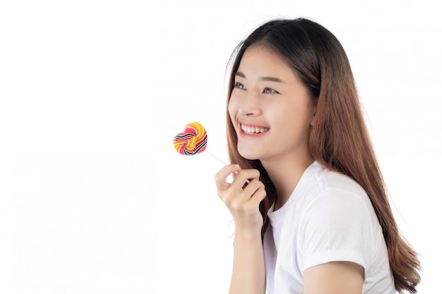 Mooie vrouw met een gelukkige glimlach die een handsuikergoed houdt, dat op witte achtergrond wordt geïsoleerd.