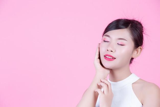 Mooie vrouw met een gezonde huid en schoonheid op een roze achtergrond.