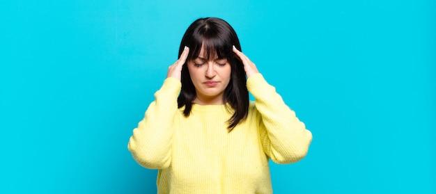 Mooie vrouw met een grote maat die er gestrest en gefrustreerd uitziet, onder druk werkt met hoofdpijn en problemen heeft