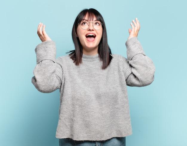 Mooie vrouw met een grote maat die zich gelukkig, verbaasd, gelukkig en verrast voelt en de overwinning viert met beide handen in de lucht
