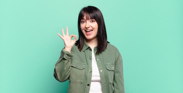 Mooie vrouw met een grote maat die zich succesvol en tevreden voelt, glimlachend met wijd open mond en goed teken met de hand maakt