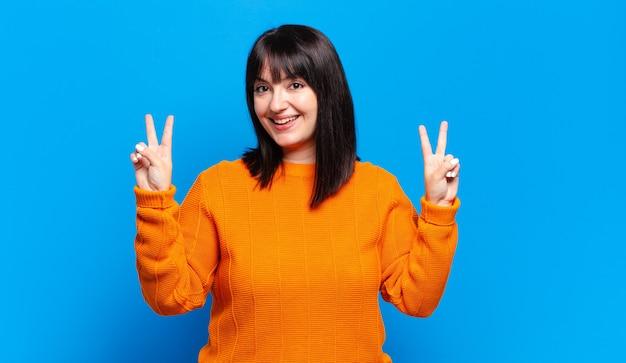 Mooie vrouw met een grote maat lacht en ziet er gelukkig, vriendelijk en tevreden uit, gebarend naar overwinning of vrede met beide handen