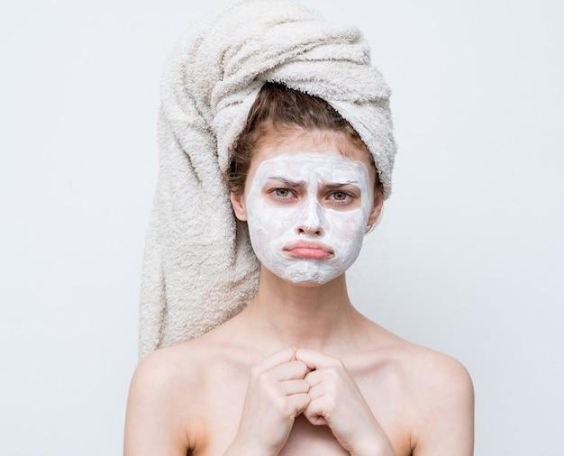 Mooie vrouw met een handdoek op haar hoofd gezichtsmasker naakte schouders aantrekkelijk.