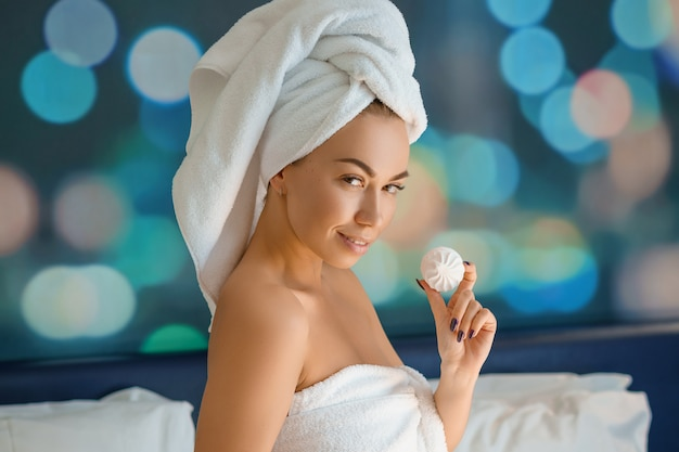 Mooie vrouw met een handdoek op haar hoofd zittend op het bed en het eten van koekjes, goedemorgen